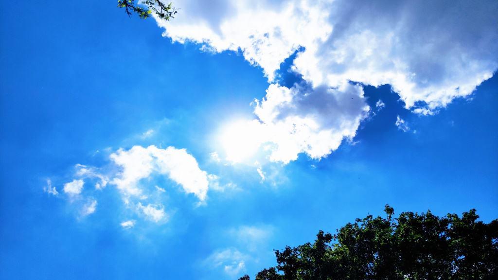 Blauer Himmel mit Wolken und Sonne im Sommer